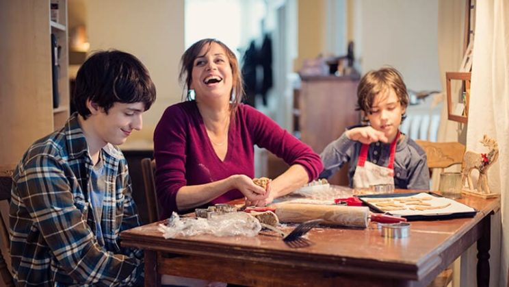 A mother and two boys making cookies at the table.