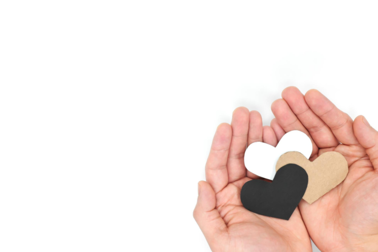 Two hands holding black, brown, white hearts.