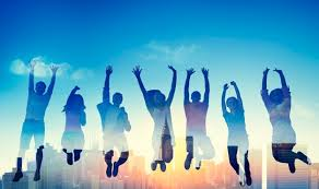 Teenagers jumping the air with arms raised to the sky