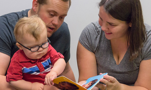 A man and woman reading a book to a small child.