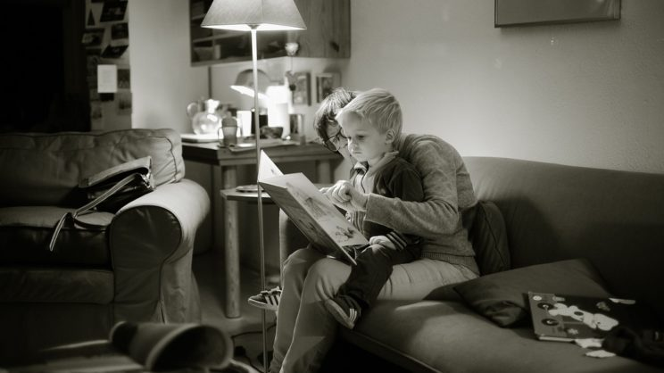 Parent reading a book with child sitting on lap