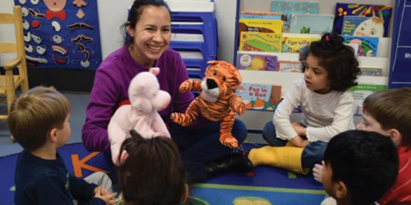 Woman playing with stuffed animals while children sit around her in a circle.