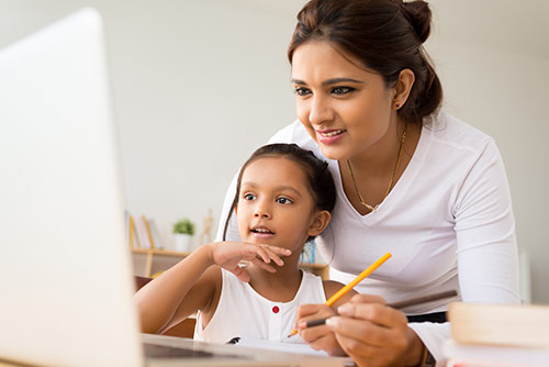Woman helping child with homework on a laptop.