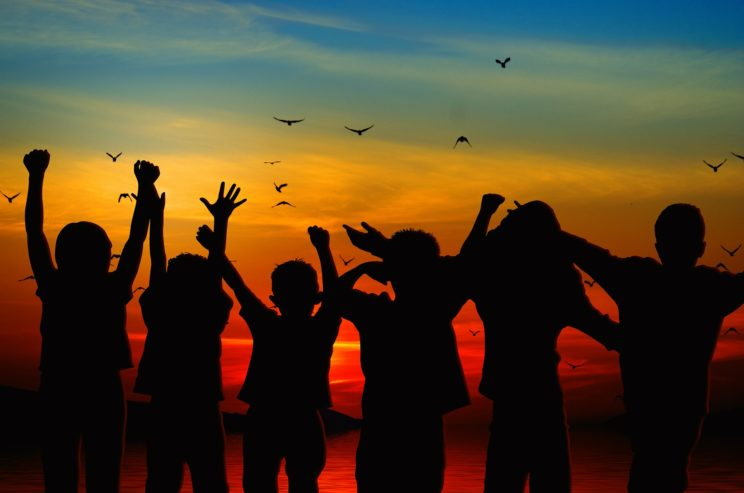 silhouette of children cheering at sunset