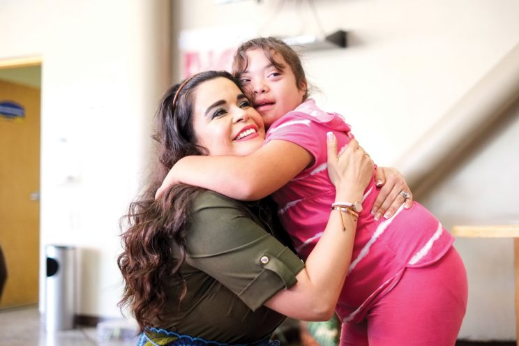 Teacher hugging student with down syndrome in school hallway.