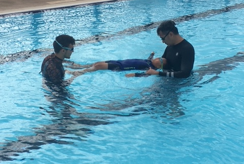 Two instructors helping a child float in a pool.
