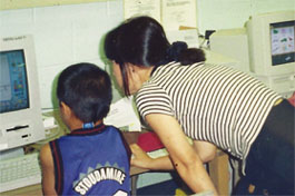 Teacher looking at a computer screen with a student.