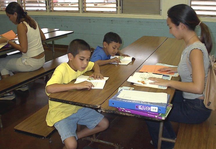 Ace Reading: Two kids and a teacher reading in a cafeteria