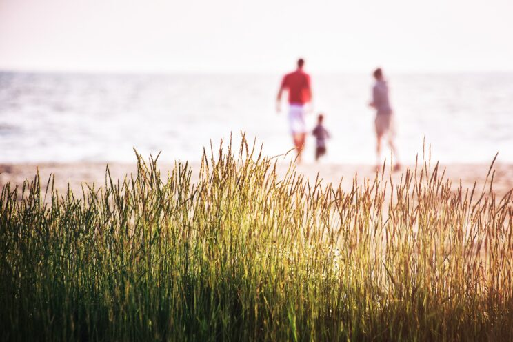 Parents and a child walking on the beach.