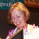 Jennifer Lang receiving an award with a lei on.