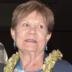Laura Poell smiling with lei around her neck.